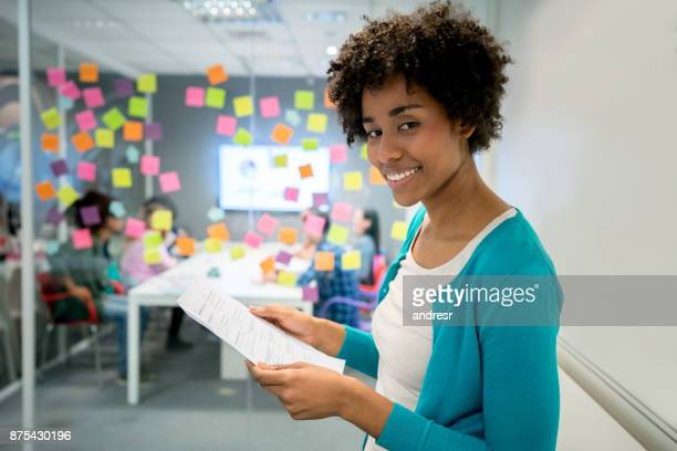 Beautiful latin american manager holding a document at the office looking at camera smiling