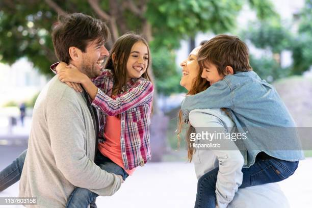 beautiful latin american parents carrying their son and daughter on back while laughing - hispanolistic stock photos and pictures