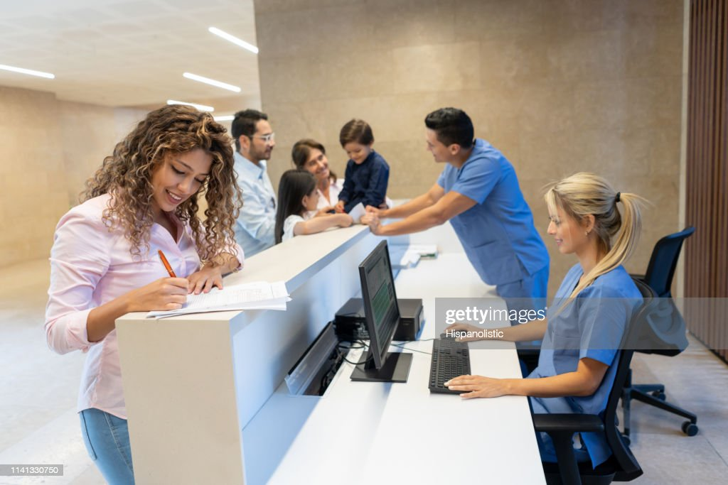 Beautiful latin american patient filling in a form at the hospital's front desk all smiling : Stock Photo