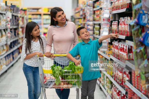 beautiful latin american single parent with her two kids at the supermarket shopping for groceries and boy pointing at something - supermarket stock pictures, royalty-free photos & images