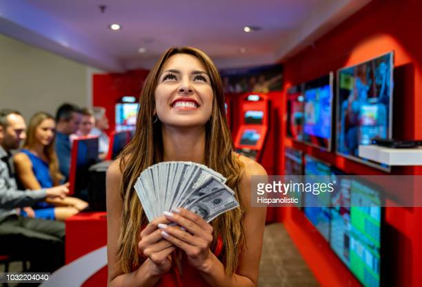 Beautiful latin american woman holding a lot of money from winning at the casino looking up daydreaming