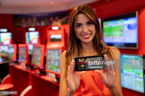 Schöne Lateinamerikanische Frau hält eine Smartphone mit einem live-Sportwetten-Anwendung