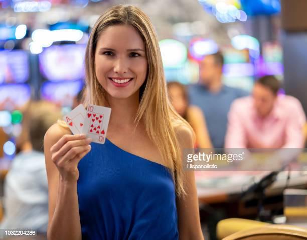Schöne Lateinamerikanische Frau halten ein Ass und eine zehn im Casino beim Blick auf die Kamera zu Lächeln