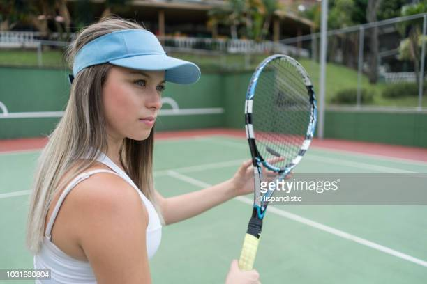 beautiful latin american woman playing tennis looking very serious - tennis player stock pictures, royalty-free photos & images