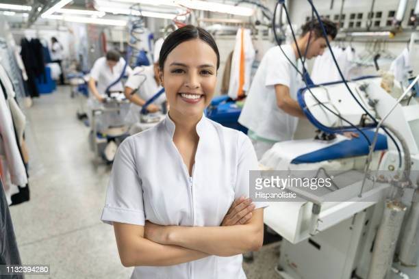 beautiful latin american young supervisor at an industrial laundry service smiling at camera with arms crossed - laundry stock pictures, royalty-free photos & images