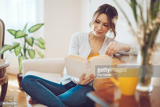 Beautiful latin woman reading a book at home