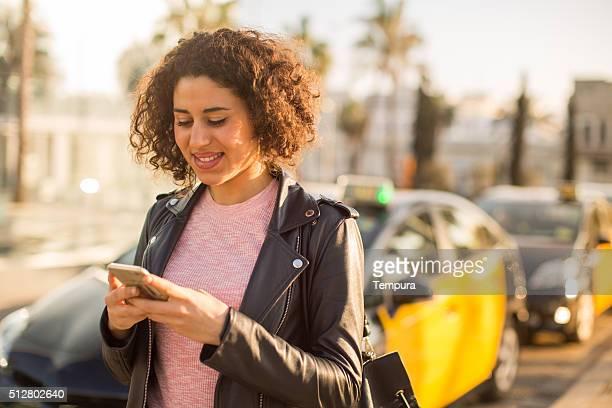 美しい女性のアプリを使用して、ラテンタクシーのバルセロナで