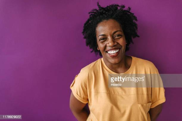 beautiful laughter in front of purple wall - colored background stock pictures, royalty-free photos & images