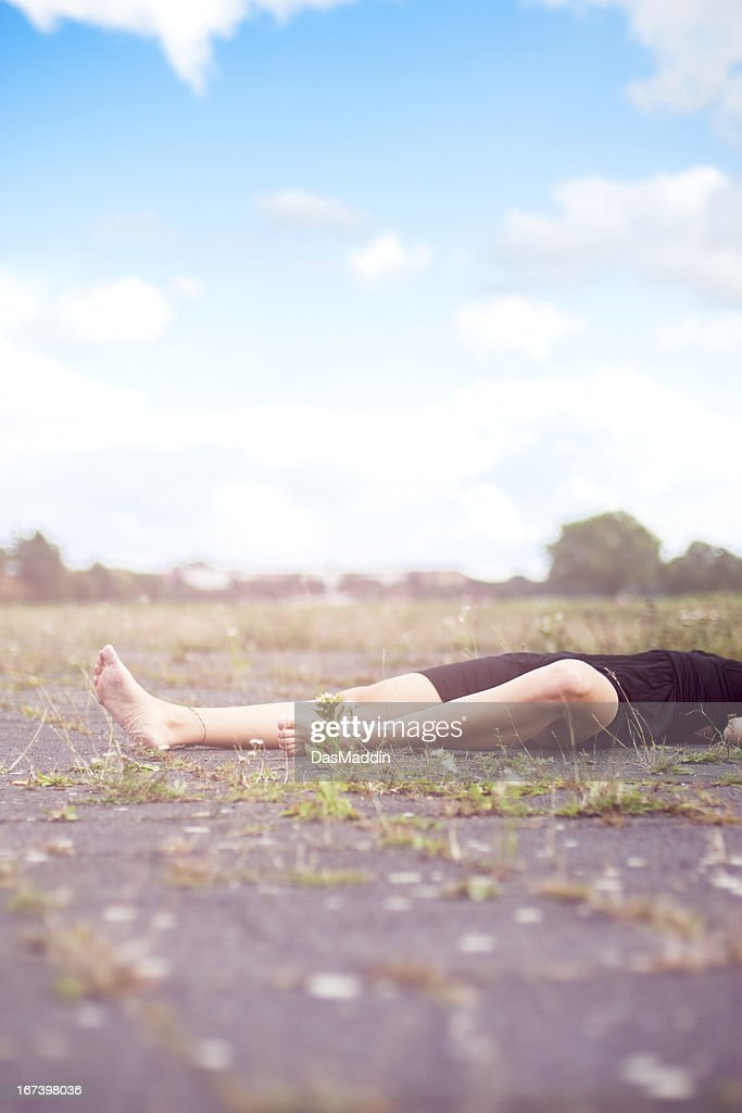 Beautiful legs of a young girl laying on the ground : Stock Photo