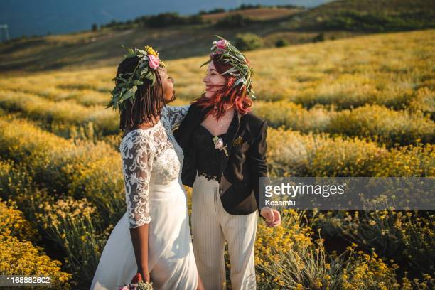 beautiful lesbian boho brides in love on meadow on their wedding day - civil partnership stock pictures, royalty-free photos & images