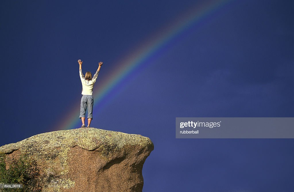 beautiful lifestyle shot of a young adult female as she stands on a rock under a rainbow : Stockfoto