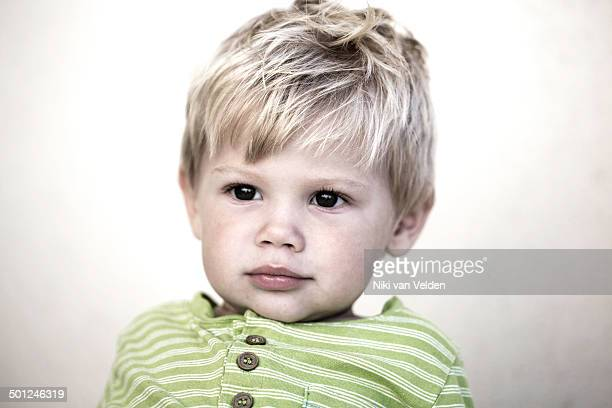 Beautiful little blond boy with dreamy expression