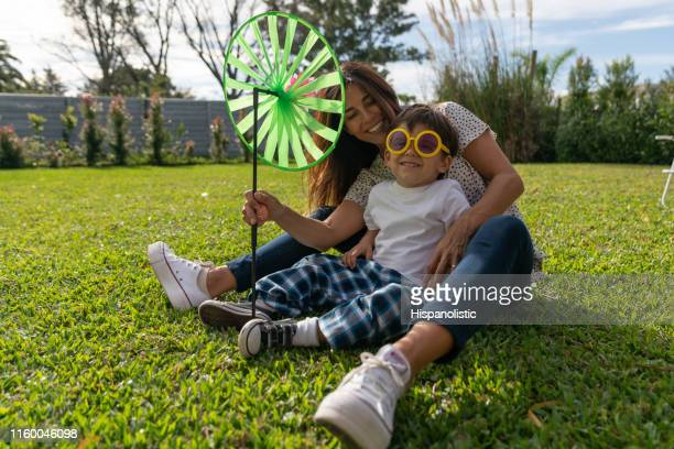 beautiful little boy and mother sitting on grass at the park having fun laughing - hispanolistic stock photos and pictures