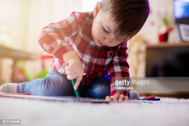 Beautiful little boy enjoying drawing at the floor