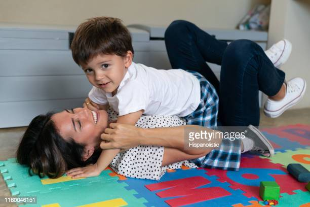 beautiful little boy lying on his mother's tummy very playfully while smiling - hispanolistic stock photos and pictures