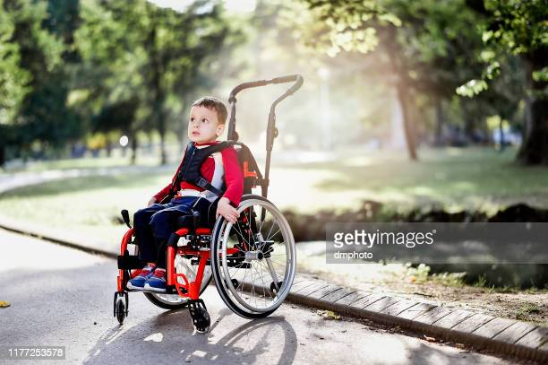 beautiful little boy on wheelchair in the park - assistive technology stock pictures, royalty-free photos & images