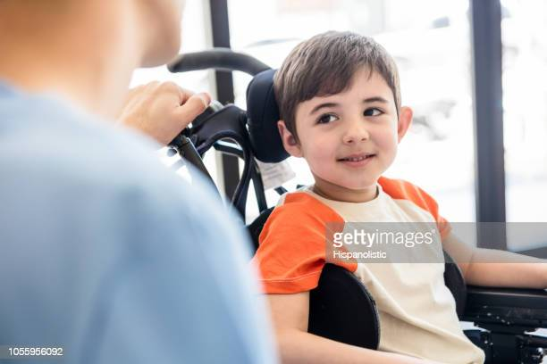 beautiful little boy on wheelchair smiling and looking with admiration at his unrecongizable physical therapist - wheelchair stock pictures, royalty-free photos & images