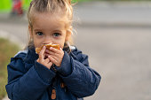 A beautiful little Caucasian girl with blond hair and eating bread eagerly with her hands looks at the camera with sad eyes