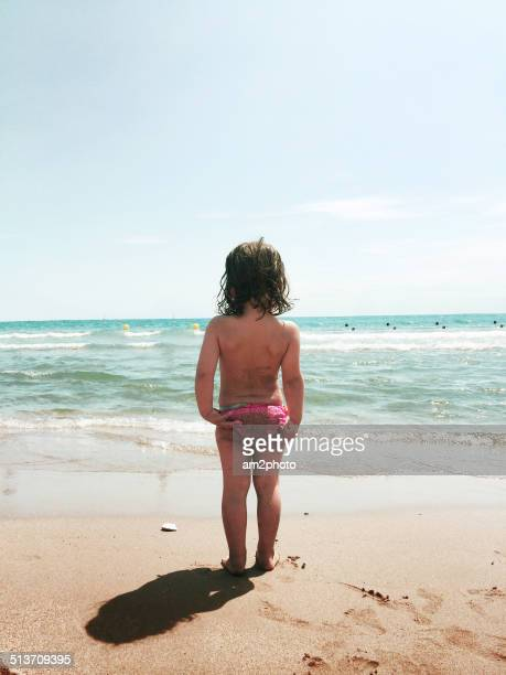 Beautiful little girl at the beach enjoying view