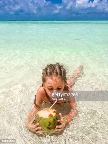 Beautiful Little Girl Drinking Coconut On The Beach
