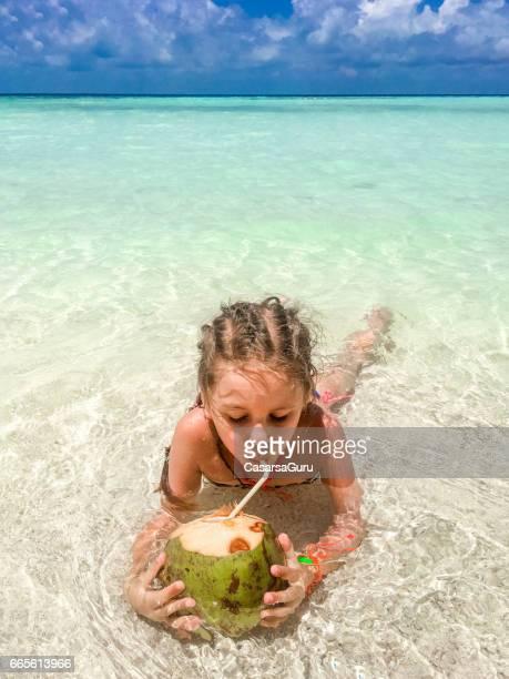 Wunderschönes kleines Mädchen trinken Kokosnuss am Strand