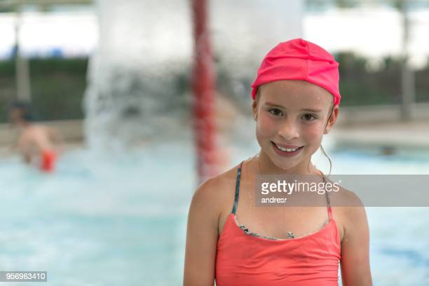 Beautiful little girl enjoying a day at the pool looking at camera smiling