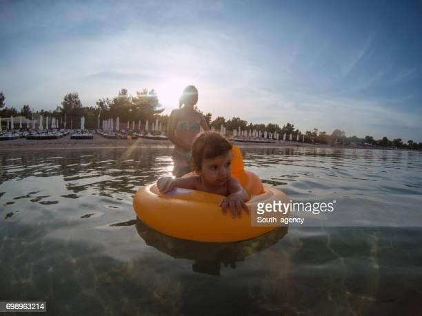 Wunderschönes kleines Mädchen auf dem Wasser schwimmt