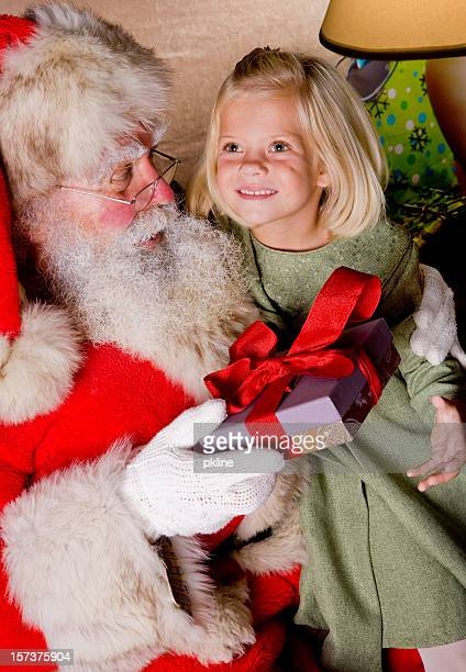 beautiful little girl gets a gift from santa - santa face stock photos and pictures