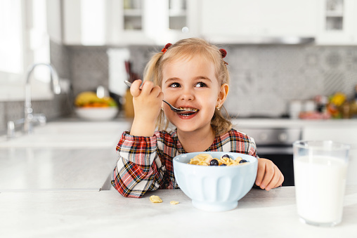 Beautiful little girl having breakfast with cereal, milk and blueberry in kitchen 1140365915
