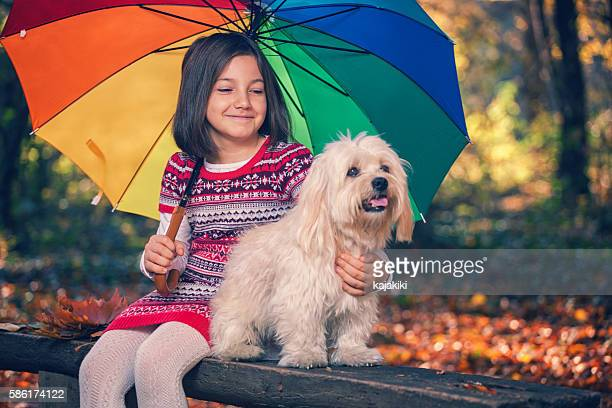 Beautiful little girl having fun in autumn forest