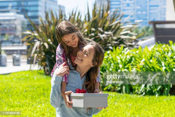 beautiful little girl holding a gift for her mom as she embraces her from the back - hispanolistic stock photos and pictures