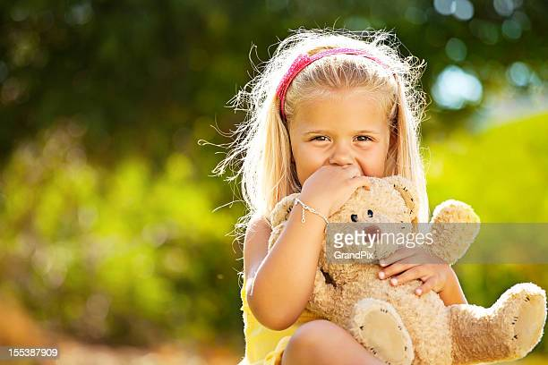 Beautiful little girl holding a teddy bear