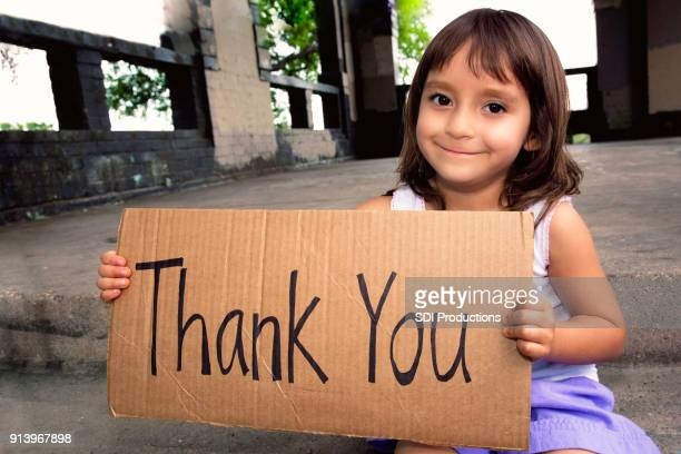 beautiful little girl holds 'thank you' sign - orphan stock pictures, royalty-free photos & images