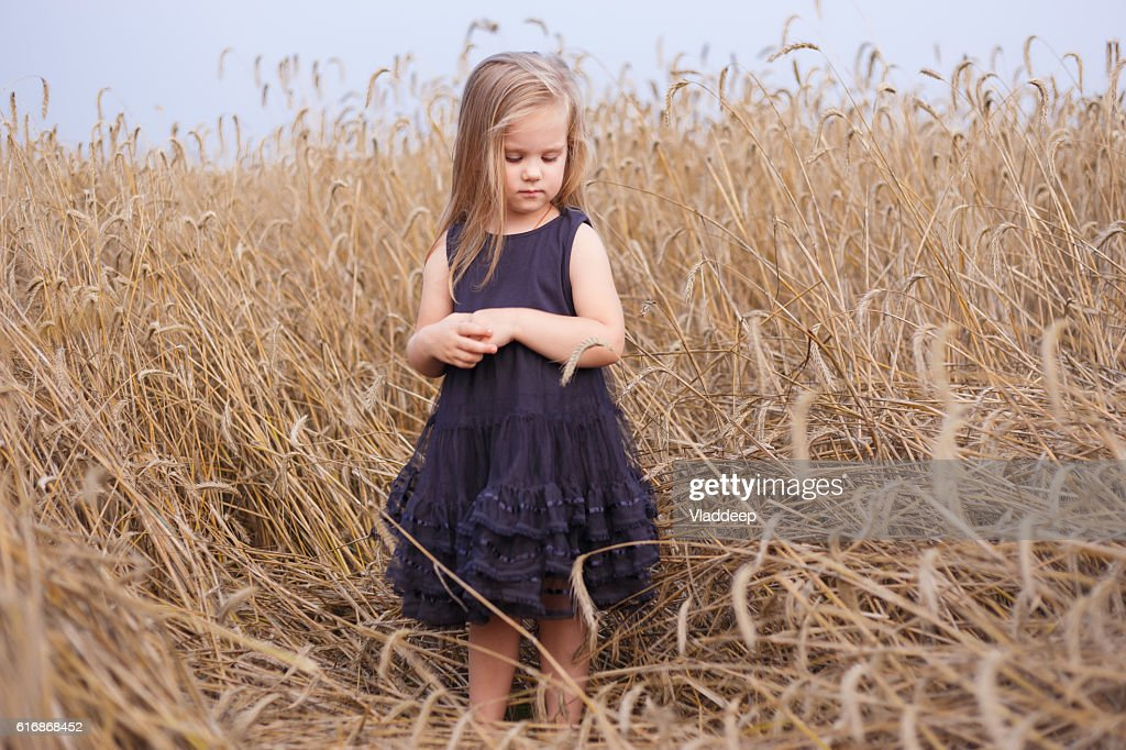 Beautiful little girl in ripe rye field staying in black : Stock Photo