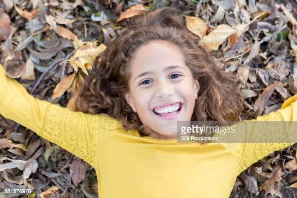 Beautiful little girl lays in fallen leaves