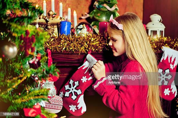 Belle petite fille à la recherche de cadeaux de Noël