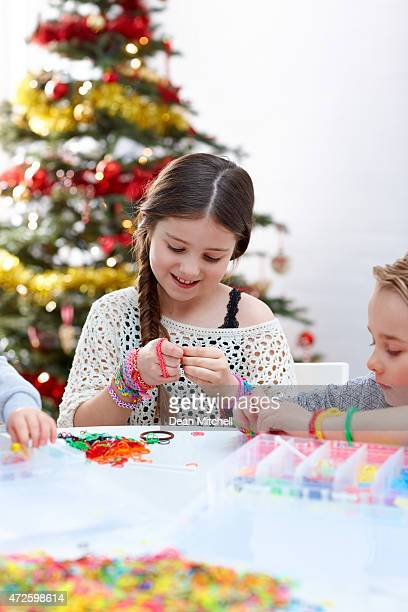 beautiful little girl making loom band bracelet with her friends - bracelet stock pictures, royalty-free photos & images