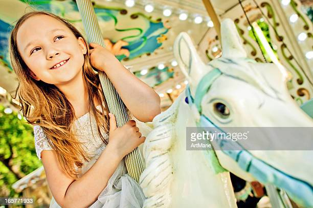 Beautiful little girl on a carousel ride