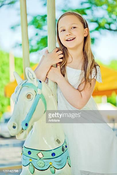 Beautiful little girl on a retro carousel ride