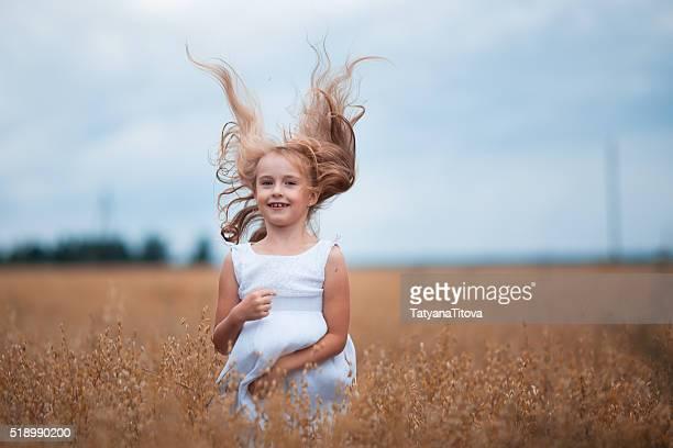 Beautiful little girl on a ripe field of oats