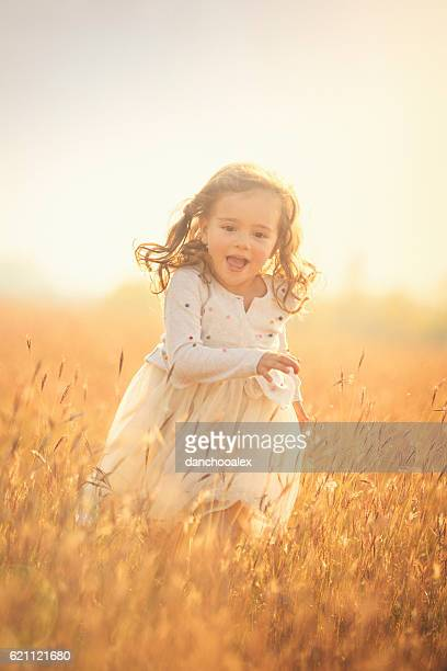 Beautiful little girl outdoor in the fields running