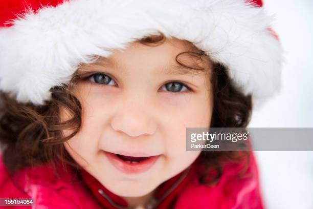 Beautiful Little Girl Playing in the Snow Wearing Santa Hat