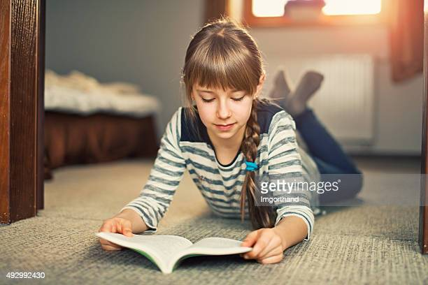 Beautiful little girl reading a book on the carpet.