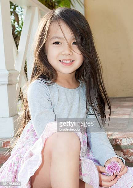 beautiful little girl sitting on front porch - model stock photos and pictures