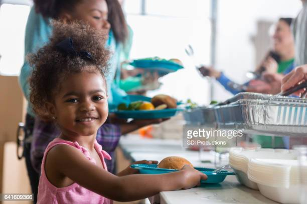 Beautiful little girl smiles while receiving meal in soup kitchen