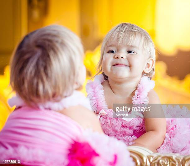 Beautiful little girl smiling at herself in a mirror