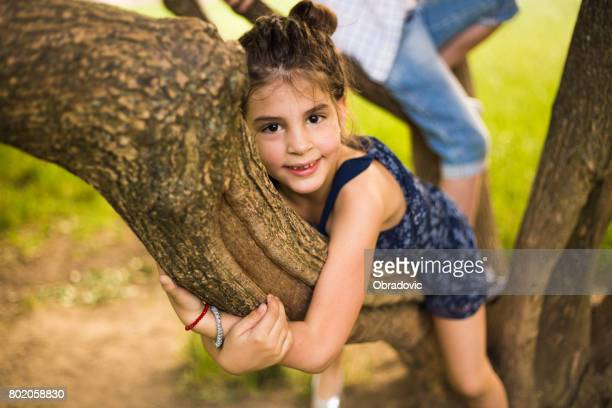 Beautiful little girl smiling hugging a tree trunk