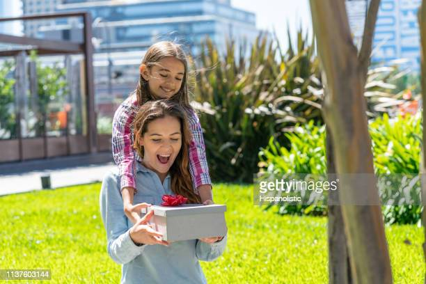 beautiful little girl surprising her mom from the back with a gift for mother's day both smiling - hispanolistic stock photos and pictures