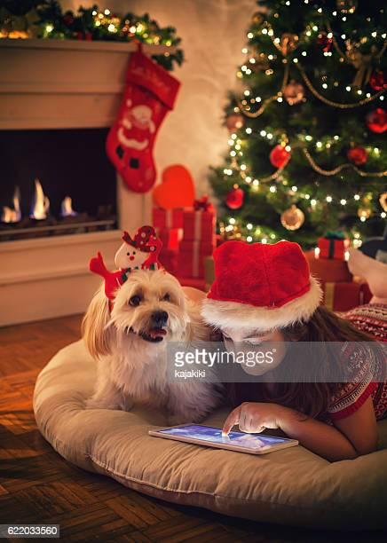 Beautiful little girl using digital tablet on Christmas night