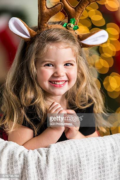Beautiful little girl wearing reindeer antlers at Christmastime